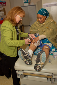 Dr. Roseanna attending to a woman's injured leg at the clinic