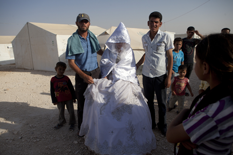Wedding family members and the groom (rt) with a 15-year-old Syrian refugee just after she left her family to travel to a nearby caravan in a refugee camp in Jordan, 5-4-13/Photo: Heidi Levine, Sipa Press