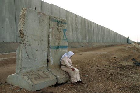 Palestinian woman rests on a cement barrier by the 1.8 mile long concrete wall along the northern West Bank, 10/11/02/Photo: Heidi Levine