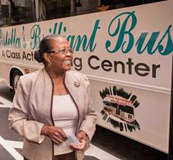 Estella Pyfrom standing in front of her Brilliant Bus mobile computer training center