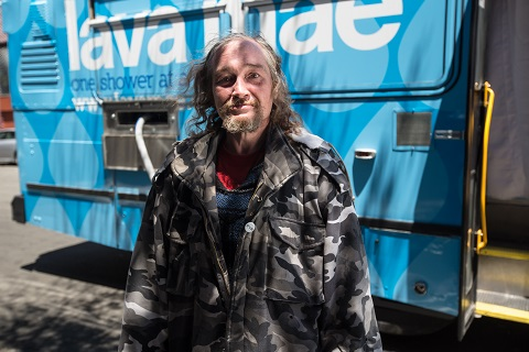 Silas in front of Lava Mae bus founded by Doniece Sandoval